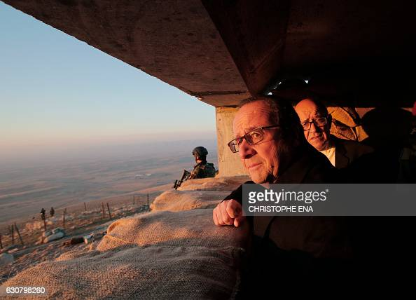 TOPSHOT French President Francois Hollande and French Defence minister JeanYves Le Drian look at Islamic Stateheld territory as they visit a military...