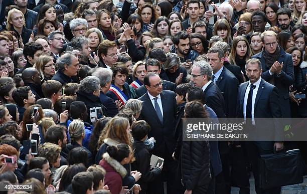 French President Francois Hollande and French Education Minister Najat VallaudBelkacem meet with people after observing a minute of silence on...