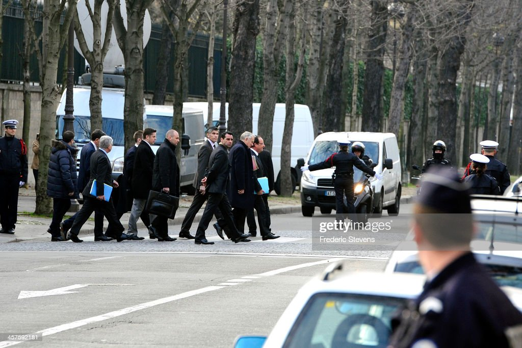 French President Francois Hollande (R) and French Prime Minister, Jean Marc Ayrault (2nd R) make their way to to the Marigny hotel for the weekly cabinet meeting on December 18, 2013 in Paris, France. The weekly cabinet meeting has been transfered to the Hotel de Marigny ahead of Christmas.