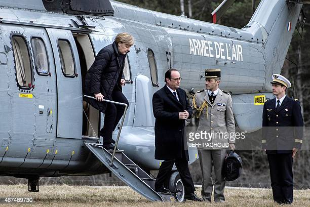 French President Francois Hollande and German Chancellor Angela Merkel disembark from a French Army helicopter near the site of the German airliner...