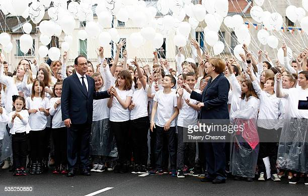 French President Francois Hollande and German Chancellor Angela Merkel attend a balloons drop with children during ceremonies to commemorate the...