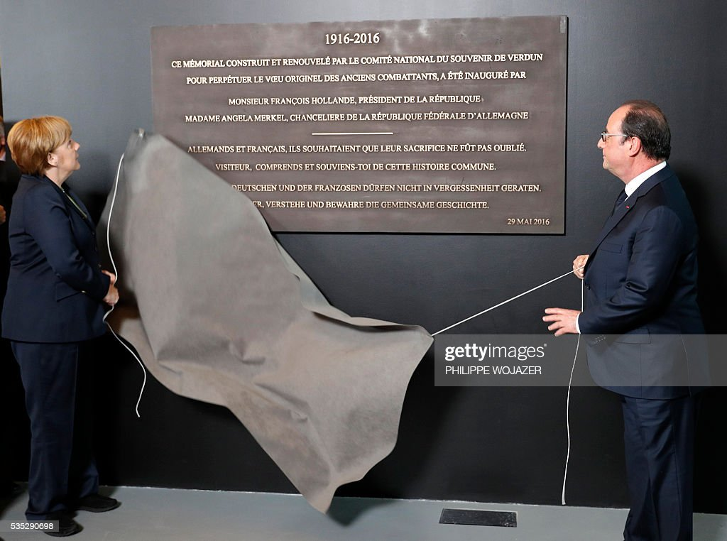 French President Francois Hollande (R) and German Chancellor Angela Merkel unveil a commemorative plaque during the inauguration of the new Verdun Memorial in Douaumont, eastern France on May 29, 2016, marking the 100th anniversary of the battle of Verdun, one of the largest battles of the First World War (WWI) on the Western Front. The battle of Verdun, in 1916, was one of the bloodiest episodes of World War I. The offensive which lasted 300 days claimed more than 300,000 lives. / AFP / POOL / PHILIPPE