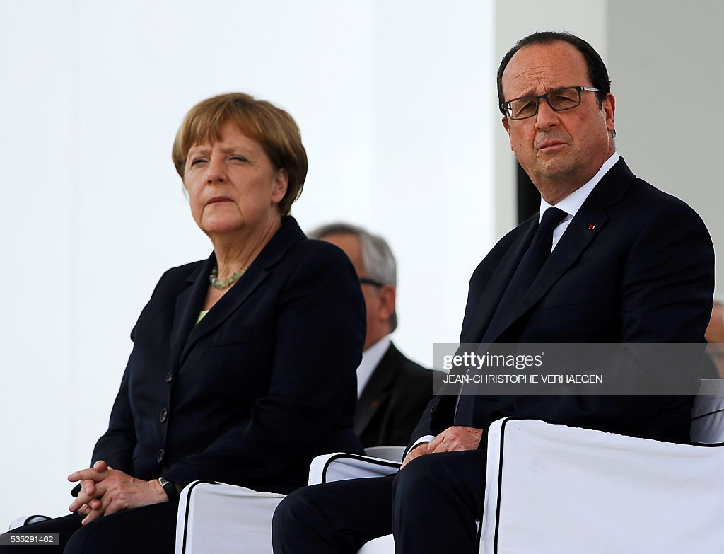 French President Francois Hollande (R) and German Chancellor Angela Merkel (R) attend a ceremony marking the centenary of the battle of Verdun, at the French National cemetery outside the Douaumont Ossuary (Ossuaire de Douaumont), northeastern France, on May 29, 2016. The battle of Verdun, in 1916, was one of the bloodiest episodes of World War I. The offensive which lasted 300 days claimed more than 300,000 lives. / AFP / POOL / JEAN