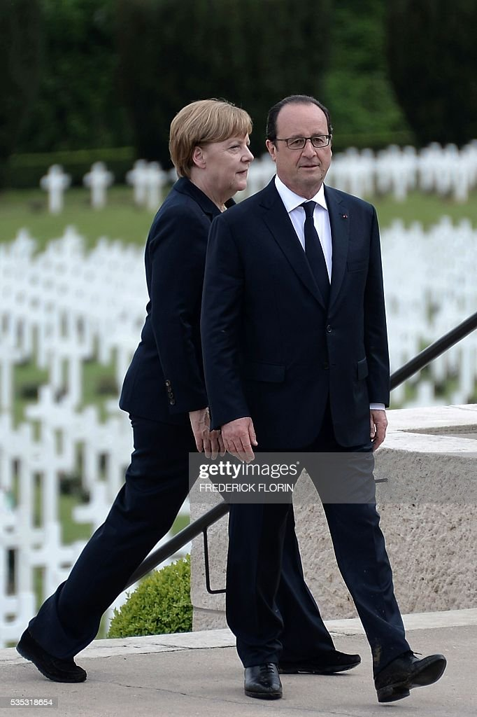 French President Francois Hollande (R) and German Chancellor Angela Merkel attend a remembrance ceremony to mark the centenary of the battle of Verdun, at the Douaumont Ossuary (Ossuaire de Douaumont), northeastern France, on May 29, 2016. The battle of Verdun, in 1916, was one of the bloodiest episodes of World War I. The offensive which lasted 300 days claimed more than 300,000 lives. / AFP / POOL / FREDERICK