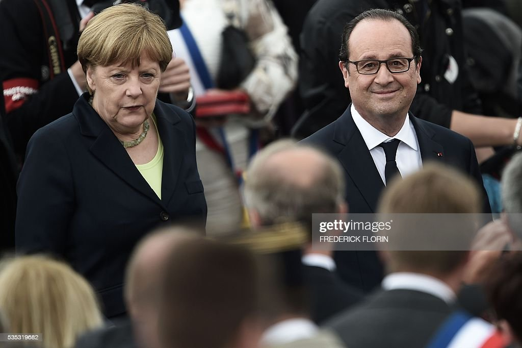 French President Francois Hollande (R) and German Chancellor Angela Merkel attend a remembrance ceremony to mark the centenary of the battle of Verdun, at the Douaumont Ossuary (Ossuaire de Douaumont), northeastern France, on May 29, 2016. The battle of Verdun, in 1916, was one of the bloodiest episodes of World War I. The offensive which lasted 300 days claimed more than 300,000 lives. / AFP / FREDERICK