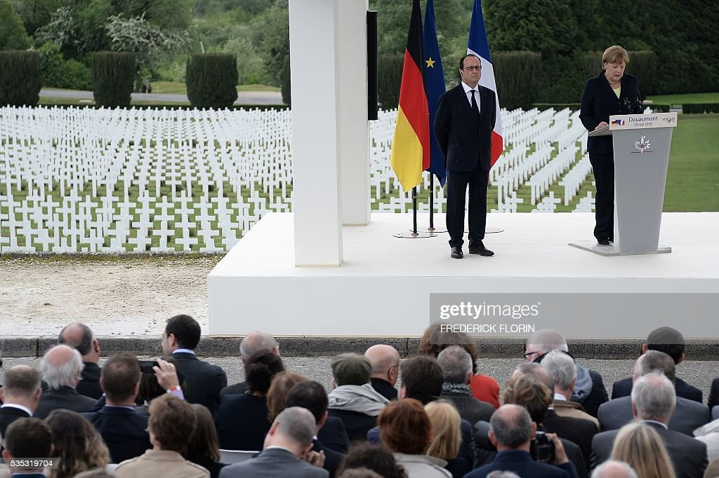 French President Francois Hollande (L) and German Chancellor Angela Merkel deliver a speech during a remembrance ceremony to mark the centenary of the battle of Verdun, at the Douaumont Ossuary (Ossuaire de Douaumont), northeastern France, on May 29, 2016. The battle of Verdun, in 1916, was one of the bloodiest episodes of World War I. The offensive which lasted 300 days claimed more than 300,000 lives. / AFP / FREDERICK