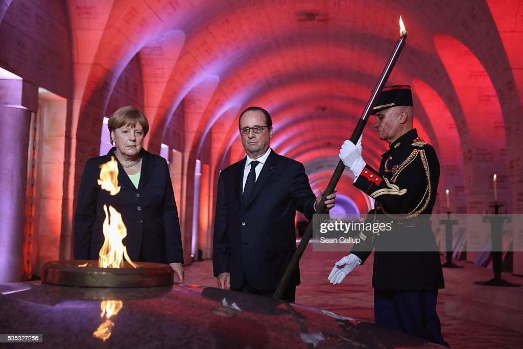 French President Francois Hollande and German Chancellor Angela Merkel finish lighting an eternal flame inside the ossuary at Douaumont in memory of the 130,000 soldiers whose remains are buried at the site during ceremonies to commemorate the 100th anniversary of the World War I Battle of Verdun on May 29, 2016 near Verdun, France. The 1916, 10-month battle pitted the French and German armies against one another in a grueling campaign of trench warfare and artillery bombardments that killed a total of approximately 300,000 soldiers. The events today coincide with the 50th anniversary of commemorations held at Verdun by then French President Charles de Gaulle and German Chancellor Konrad Adenauer that paved the way for a new era of peaceful, post-war Franco-German relations.