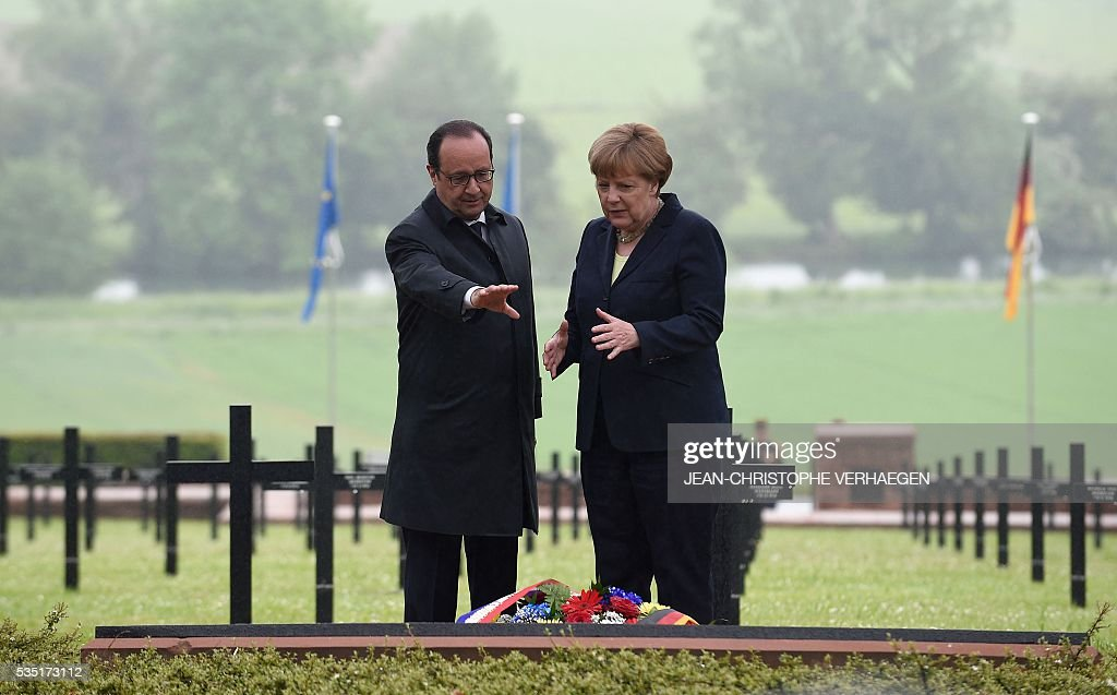 French President Francois Hollande (L) and German Chancellor Angela Merkel talks as they pay their respects after laying a wreath at a German cemetery in Consenvoye, northeastern France on May 29, 2016, during a remembrance ceremony to mark the centenary of the battle of Verdun. The battle of Verdun, in 1916, was one of the bloodiest episodes of World War I. The offensive which lasted 300 days claimed more than 300,000 lives. VERHAEGEN