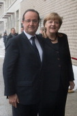 French President Francois Hollande and German Chancellor Angela Merkel arrive at the French Embassy in Berlin on January 22 2013 for a meeting as...