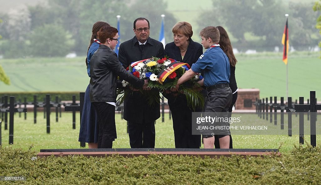 French President Francois Hollande (C-L) and German Chancellor Angela Merkel (C-R) lay a wreath at a German cemetery in Consenvoye, northeastern France on May 29, 2016, during a remembrance ceremony to mark the centenary of the battle of Verdun. The battle of Verdun, in 1916, was one of the bloodiest episodes of World War I. The offensive which lasted 300 days claimed more than 300,000 lives. VERHAEGEN