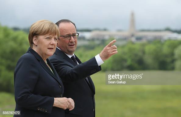 French President Francois Hollande and German Chancellor Angela Merkel look out from the terrace of the Verdun Memorial at the former Verdun...