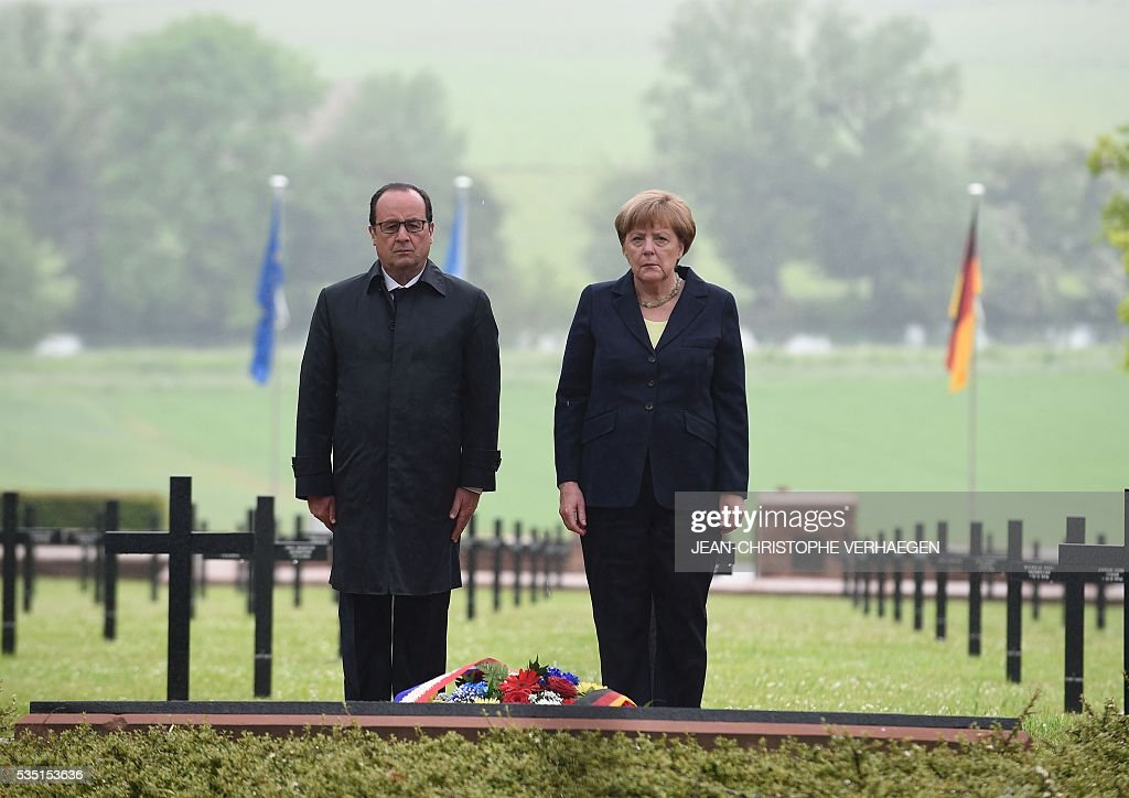 French President Francois Hollande (L) and German Chancellor Angela Merkel pay their respects at a German cemetery in Consenvoye, northeastern France on May 29, 2016, during a remembrance ceremony to mark the centenary of the battle of Verdun. The battle of Verdun, in 1916, was one of the bloodiest episodes of World War I. The offensive which lasted 300 days claimed more than 300,000 lives. VERHAEGEN