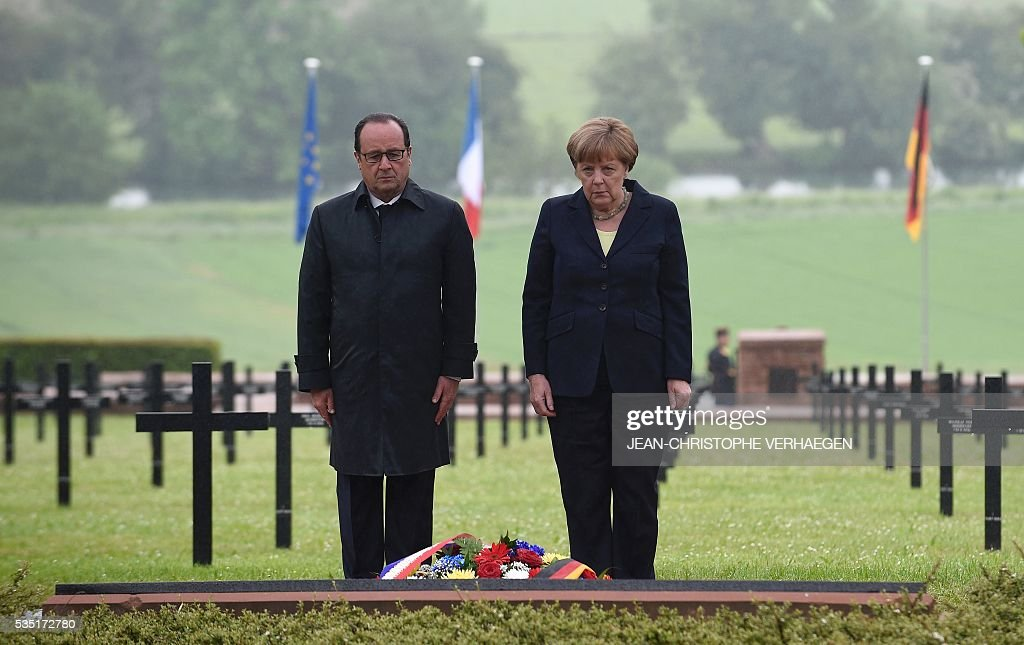 French President Francois Hollande (L) and German Chancellor Angela Merkel pay their respects after laying a wreath at a German cemetery in Consenvoye, northeastern France on May 29, 2016, during a remembrance ceremony to mark the centenary of the battle of Verdun. The battle of Verdun, in 1916, was one of the bloodiest episodes of World War I. The offensive which lasted 300 days claimed more than 300,000 lives. VERHAEGEN