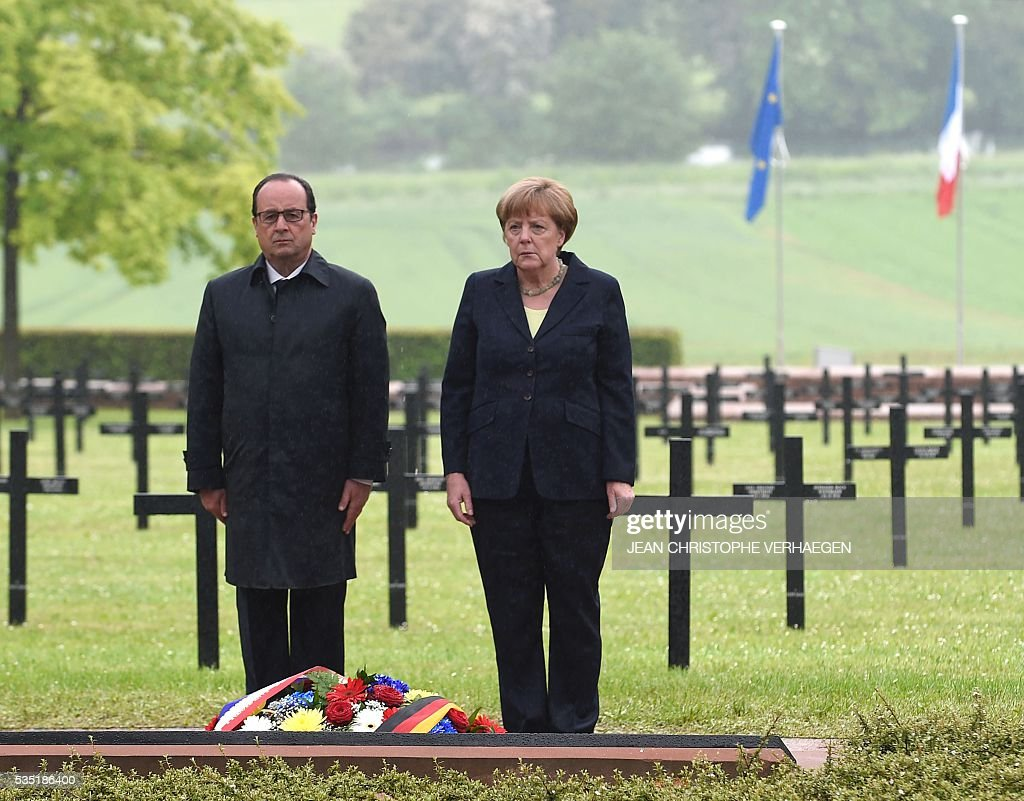 French President Francois Hollande (L) and German Chancellor Angela Merkel pay their respects after laying a wreath at a German cemetery in Consenvoye, northeastern France on May 29, 2016, during a remembrance ceremony to mark the centenary of the battle of Verdun. The battle of Verdun, in 1916, was one of the bloodiest episodes of World War I. The offensive which lasted 300 days claimed more than 300,000 lives. / AFP / POOL / Jean Christophe VERHAEGEN