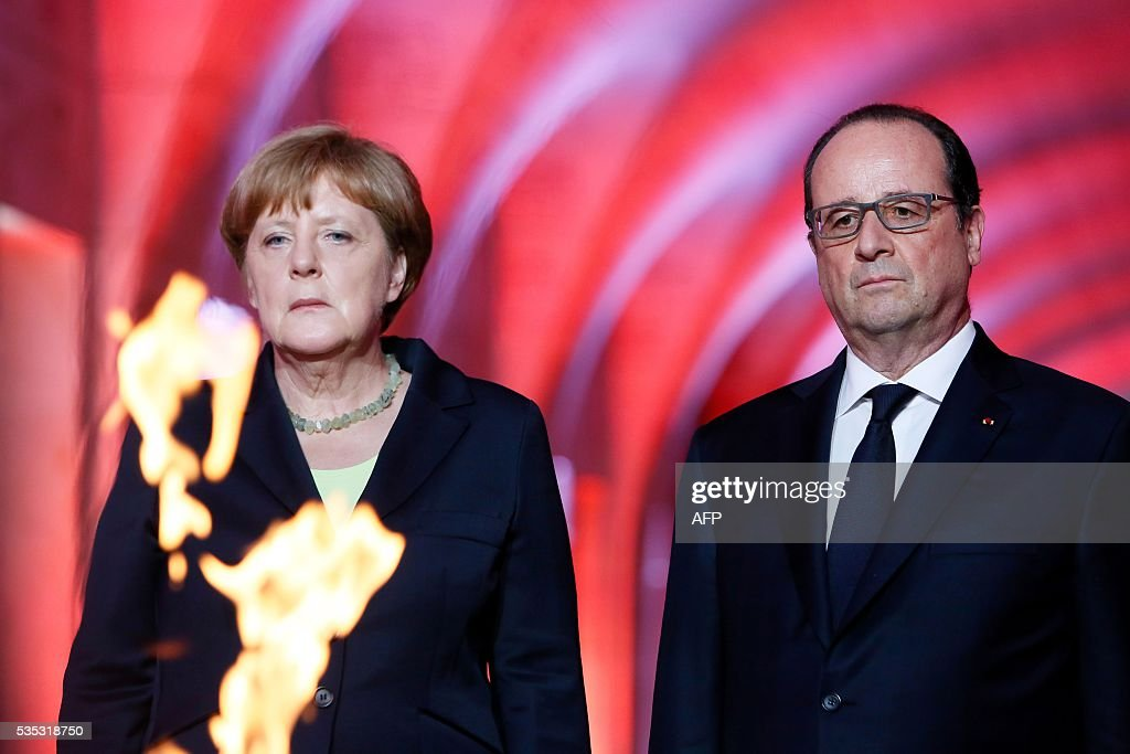 French President Francois Hollande (R) and German Chancellor Angela Merkel (L) pay their respects in front of the Eternal Flame in the Douaumont Ossuary (Ossuaire de Douaumont), northeastern France, on May 29, 2016, during a remembrance ceremony to mark the centenary of the battle of Verdun. The battle of Verdun, in 1916, was one of the bloodiest episodes of World War I. The offensive which lasted 300 days claimed more than 300,000 lives. / AFP / POOL