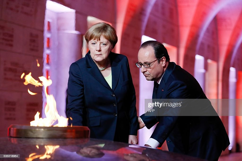 French President Francois Hollande (R) and German Chancellor Angela Merkel (L) pay their repects in front of the Eternal Flame in the Douaumont Ossuary (Ossuaire de Douaumont), northeastern France, on May 29, 2016, during a remembrance ceremony to mark the centenary of the battle of Verdun. The battle of Verdun, in 1916, was one of the bloodiest episodes of World War I. The offensive which lasted 300 days claimed more than 300,000 lives. / AFP / POOL