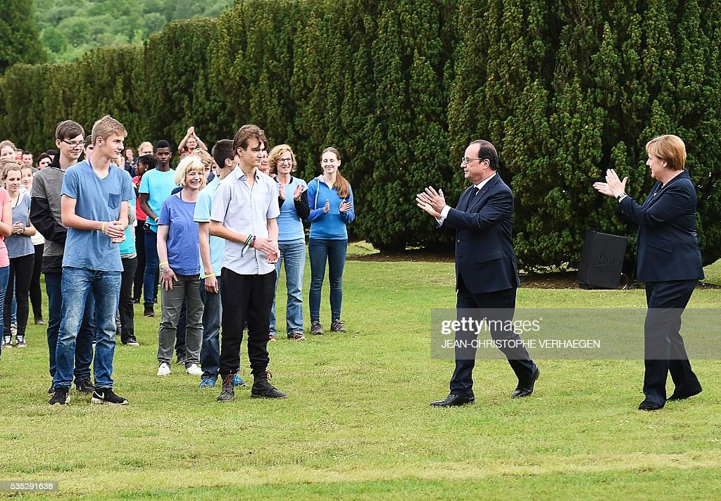 French President Francois Hollande (2nd R) and German Chancellor Angela Merkel (R) applaud French and German youths after a show at the French National cemetery outside the Douaumont Ossuary (Ossuaire de Douaumont), northeastern France, on May 29, 2016, during a remembrance ceremony to mark the centenary of the battle of Verdun. The battle of Verdun, in 1916, was one of the bloodiest episodes of World War I. The offensive which lasted 300 days claimed more than 300,000 lives. / AFP / POOL / JEAN