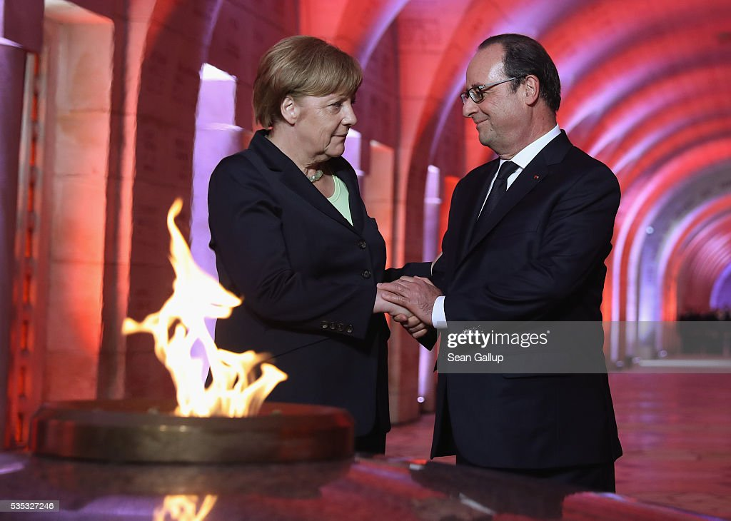 French President Francois Hollande and German Chancellor <a gi-track='captionPersonalityLinkClicked' href=/galleries/search?phrase=Angela+Merkel&family=editorial&specificpeople=202161 ng-click='$event.stopPropagation()'>Angela Merkel</a> shake hands after lighting an eternal flame inside the ossuary at Douaumont in memory of the 130,000 soldiers whose remains are buried at the site during ceremonies to commemorate the 100th anniversary of the World War I Battle of Verdun on May 29, 2016 near Verdun, France. The 1916, 10-month battle pitted the French and German armies against one another in a grueling campaign of trench warfare and artillery bombardments that killed a total of approximately 300,000 soldiers. The events today coincide with the 50th anniversary of commemorations held at Verdun by then French President Charles de Gaulle and German Chancellor Konrad Adenauer that paved the way for a new era of peaceful, post-war Franco-German relations.