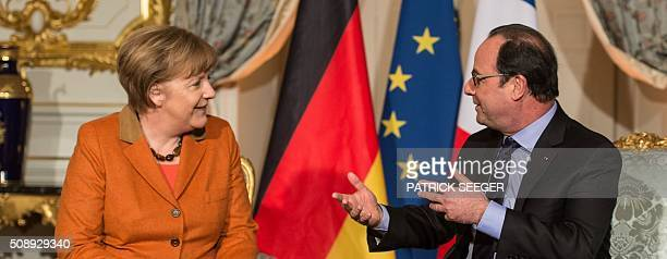 French President Francois Hollande and German Chancellor Angela Merkel talk together at the Prefecture in Strasbourg eastern France on February 7...