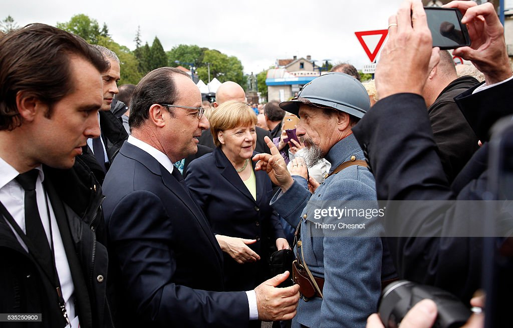 French President Francois Hollande and German Chancellor <a gi-track='captionPersonalityLinkClicked' href=/galleries/search?phrase=Angela+Merkel&family=editorial&specificpeople=202161 ng-click='$event.stopPropagation()'>Angela Merkel</a> talk with a history reenactor dressed as World War I French soldier during ceremonies to commemorate the 100th anniversary of the World War I Battle of Verdun on May 29, 2016 near Verdun, France. The 1916, 10-month battle pitted the French and German armies against one another in a gruelling campaign of trench warfare and artillery bombardments that killed a total of approximately 300,000 soldiers. The events today coincide with the 50th anniversary of commemorations held at Verdun by then French President Charles de Gaulle and German Chancellor Konrad Adenauer that paved the way for a new era of peaceful, post-war Franco-German relations.
