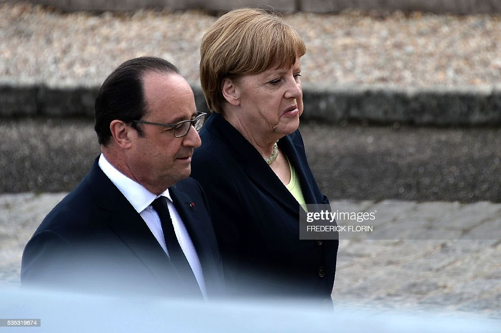 French President Francois Hollande (L) and German Chancellor Angela Merkel talk as they attend a remembrance ceremony to mark the centenary of the battle of Verdun, at the Douaumont Ossuary (Ossuaire de Douaumont), northeastern France, on May 29, 2016. The battle of Verdun, in 1916, was one of the bloodiest episodes of World War I. The offensive which lasted 300 days claimed more than 300,000 lives. / AFP / FREDERICK