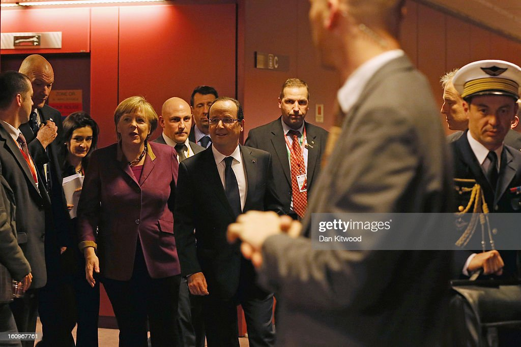 French President Francois Hollande (R) and German Chancellor Angela Merkel (L) arrive to address the media at the headquarters of the Council after reaching a deal on the budget for 2014-20 on February 8, 2013 in Brussels, Belgium. EU leaders have set out the framework for agreeing on a 2014-2020 EU budget, during talks that continued through the night at the European Council meetings in Brussels. The historic deal would see a 34.4 billion Euros cut to EU spending over the next 7 year period.