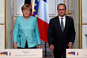 French President Francois Hollande and German Chancellor Angela Merkel arrive to give a press conference after their meeting at the Elysee Palace on...