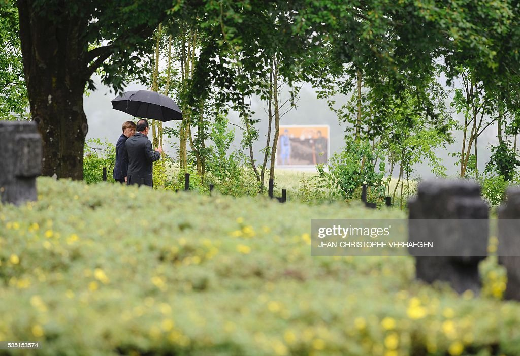 French President Francois Hollande (2ndL) and German Chancellor Angela Merkel (L) walk at a German cemetery in Consenvoye, northeastern France on May 29, 2016, during a remembrance ceremony to mark the centenary of the battle of Verdun. The battle of Verdun, in 1916, was one of the bloodiest episodes of World War I. The offensive which lasted 300 days claimed more than 300,000 lives. VERHAEGEN