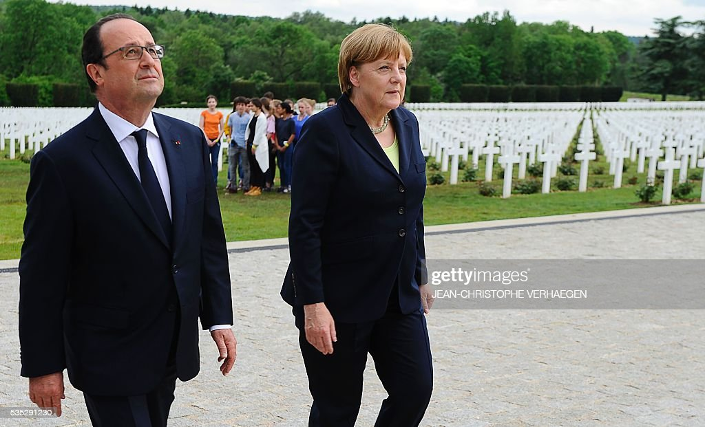 French President Francois Hollande (L) and German Chancellor Angela Merkel (R) walk at the French National cemetery outside the Douaumont Ossuary (Ossuaire de Douaumont), northeastern France, on May 29, 2016, during a remembrance ceremony to mark the centenary of the battle of Verdun. The battle of Verdun, in 1916, was one of the bloodiest episodes of World War I. The offensive which lasted 300 days claimed more than 300,000 lives. / AFP / POOL / JEAN