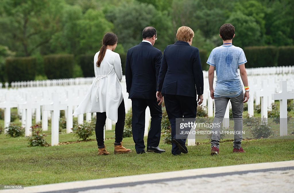 French President Francois Hollande (2nd L) and German Chancellor Angela Merkel (2nd R) walk with two youths from Verdun at the French National cemetery outside the Douaumont Ossuary (Ossuaire de Douaumont), northeastern France, on May 29, 2016, during a remembrance ceremony to mark the centenary of the battle of Verdun. The battle of Verdun, in 1916, was one of the bloodiest episodes of World War I. The offensive which lasted 300 days claimed more than 300,000 lives. / AFP / POOL / JEAN