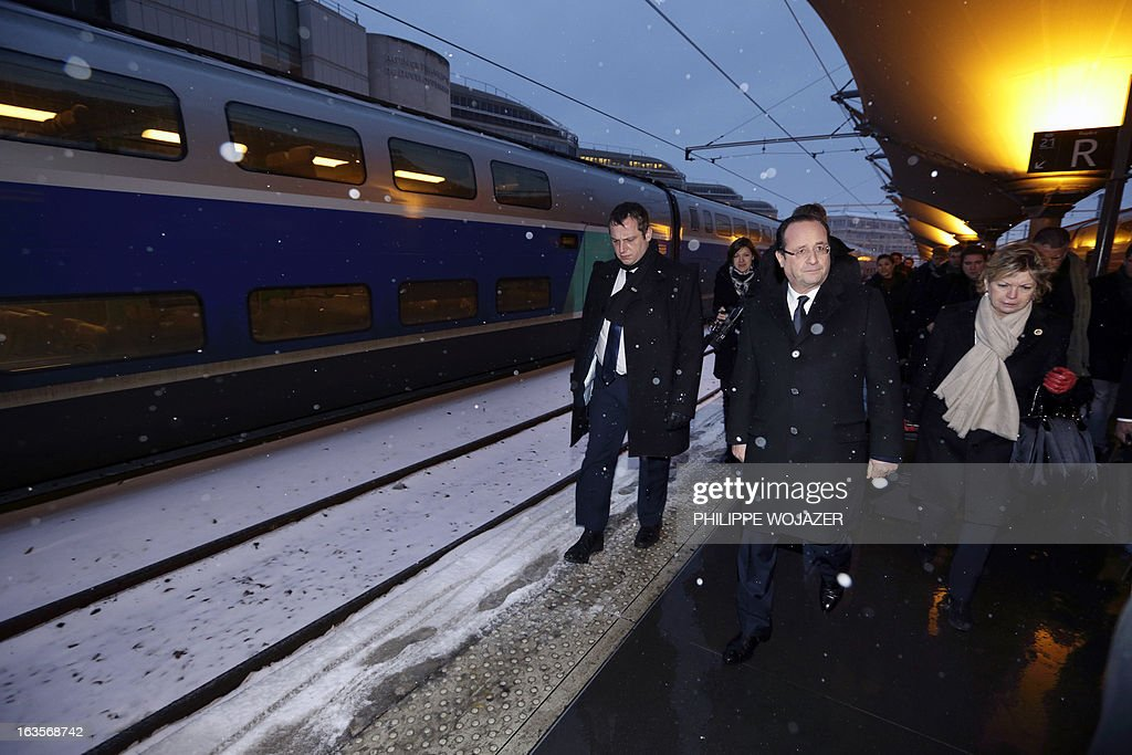 French President Francois Hollande (C) and his cabinet chief Sylvie Hubac (R) arrive at Paris Lyon railway station on March 12, 2013 following a two-day visit to the Burgundy region. WOJAZER