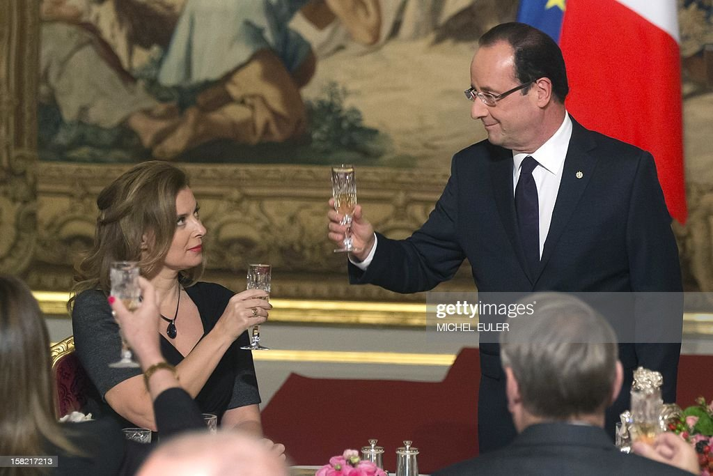 French President Francois Hollande (R) and his companion Valerie Trierweiler (L) toast during a state dinner with Brazilian President at the Elysee Palace in Paris, on December 11, 2012. Brazil's President Dilma Rousseff is on a two-day visit to France.