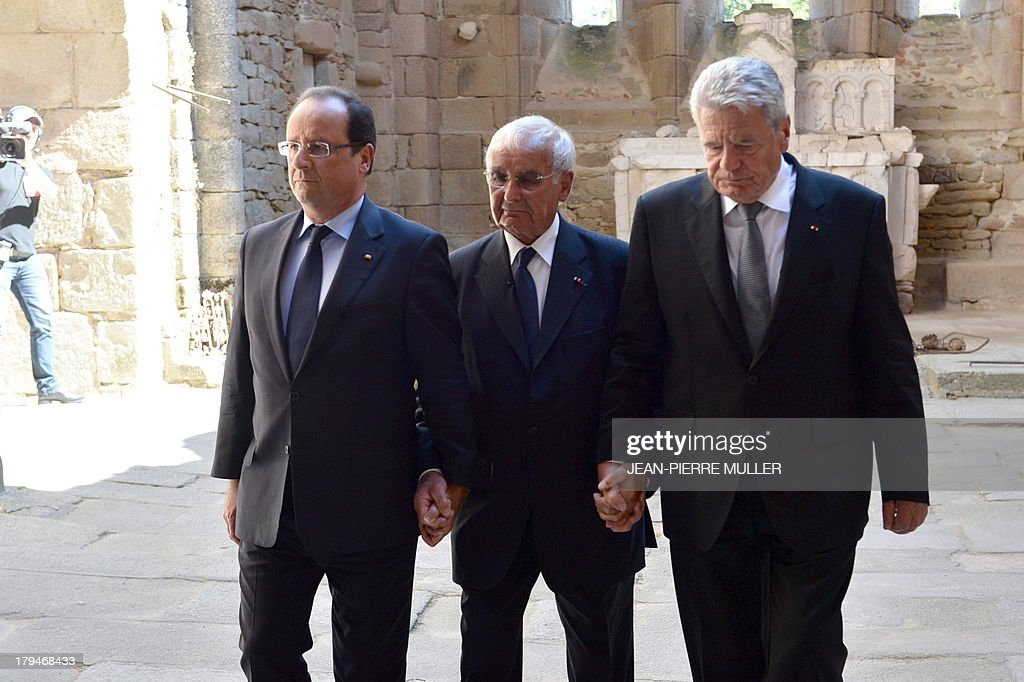 French President Francois Hollande (L) and his German counterpart Joachim Gauck (R) hold hands on September 4, 2013 with Robert Hebras, 88, one of the last survivors of the World War II massacre in Oradour-sur-Glane, in the ruins of the church in the central French village. The town has become a ghostly war crimes museum since Nazi troops burnt it to the ground on June 10, 1944. Six hundred and forty-two original inhabitants were massacred in Oradour and no one knows exacty why. Women and chldren were massacred in the church before their bodies were burnt by a German SS division. Hebras is one of three survivors still alive.