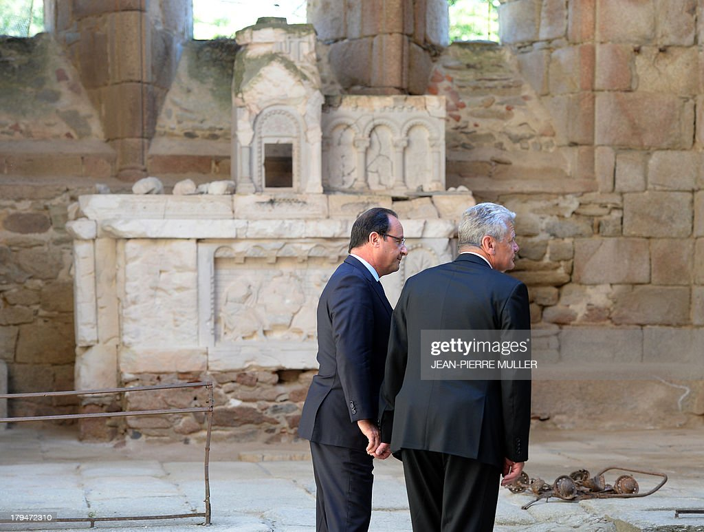French President Francois Hollande (L) and his German counterpart Joachim Gauck (R) hold hands on September 4, 2013 in the ruins of the church of the central French village of Oradour-sur-Glane, which has become a ghostly war crimes museum since Nazi troops burnt it to the ground on June 10, 1944. Six hundred and forty-two original inhabitants were massacred in Oradour and no one knows exacty why. Women and chldren were massacred in the church before their bodies were burnt by a German SS division. Hebras is one of three survivors still alive.