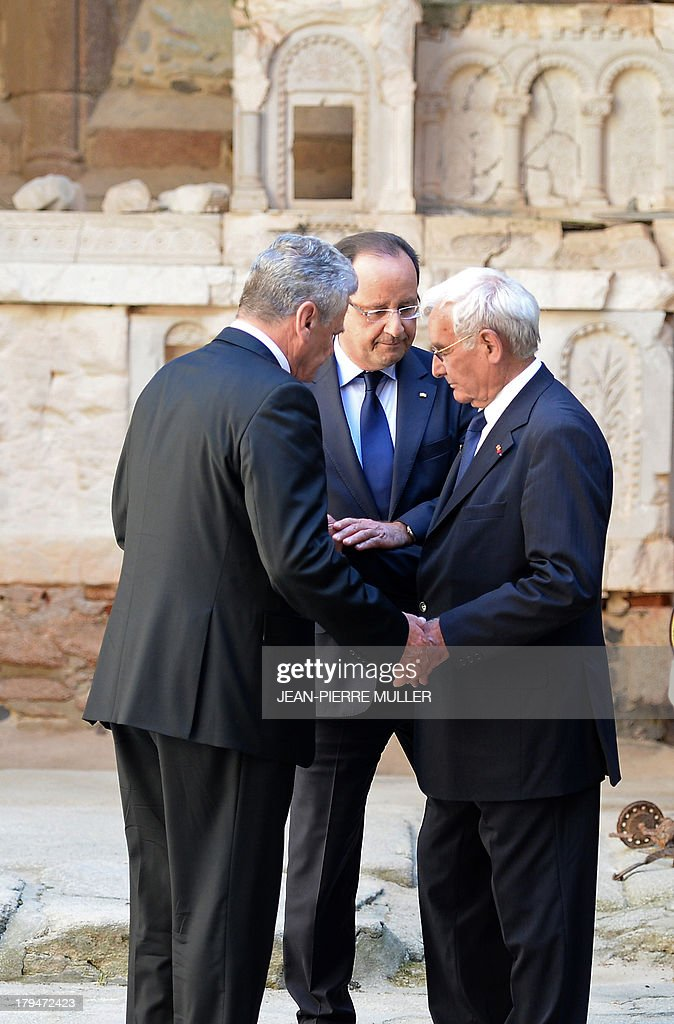 French President Francois Hollande (C) and his German counterpart Joachim Gauck (L) hold hands on September 4, 2013 with Robert Hebras (R), 88, one of the last survivors of the World War II massacre in Oradour-sur-Glane, in the ruins of the church in the central French village. The town has become a ghostly war crimes museum since Nazi troops burnt it to the ground on June 10, 1944. Six hundred and forty-two original inhabitants were massacred in Oradour and no one knows exacty why. Women and chldren were massacred in the church before their bodies were burnt by a German SS division. Hebras is one of three survivors still alive. AFP PHOTO / POOL / JEAN-PIERRE MULLER