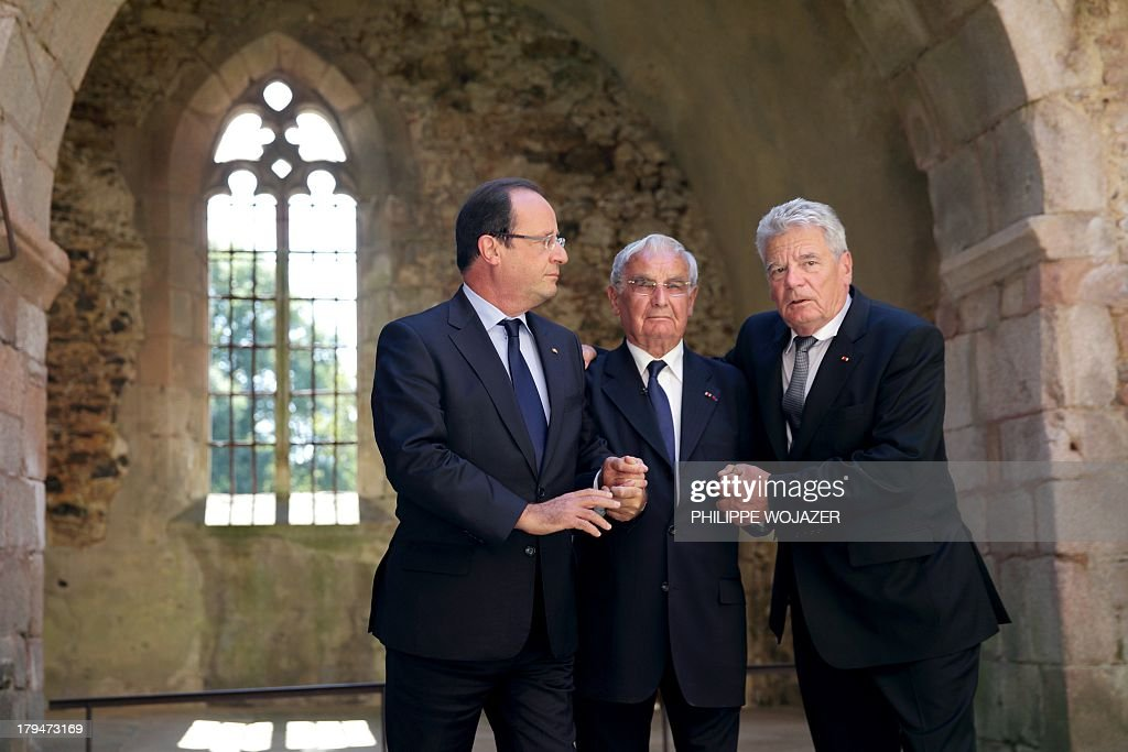 French president Francois Hollande (L) and his German counterpart Joachim Gauck (R) hold hands on September 4, 2013 in the ruins of the church of Oradour-sur-Glane with Robert Hebras, 88, one of the last survivors of the World War II massacre in the central French village. The town has become a ghostly war crimes museum since Nazi troops burnt it to the ground on June 10, 1944. Six hundred and forty-two original inhabitants were massacred in Oradour and no one knows exacty why. Women and chldren were massacred in the church before their bodies were burnt by a German SS division. Hebras is one of three survivors still alive.