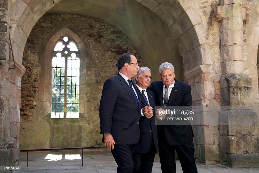 French president Francois Hollande (L) and his German counterpart Joachim Gauck (R) hold hands on September 4, 2013 in the ruins of the church of Oradour-sur-Glane with Robert Hebras, 88, one of the last survivors of the World War II massacre in the central French village. The town has become a ghostly war crimes museum since Nazi troops burnt it to the ground on June 10, 1944. Six hundred and forty-two original inhabitants were massacred in Oradour and no one knows exacty why. Women and chldren were massacred in the church before their bodies were burnt by a German SS division. Hebras is one of three survivors still alive. AFP PHOTO / POOL / PHILIPPE WOJAZER