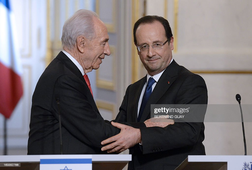 French President Francois Hollande (R) and his Israeli counterpart Shimon Peres hold each other at the end of a joint press conference after a meeting at the Elysee presidential palace on March 8, 2013 in Paris. AFP PHOTO / BERTRAND GUAY