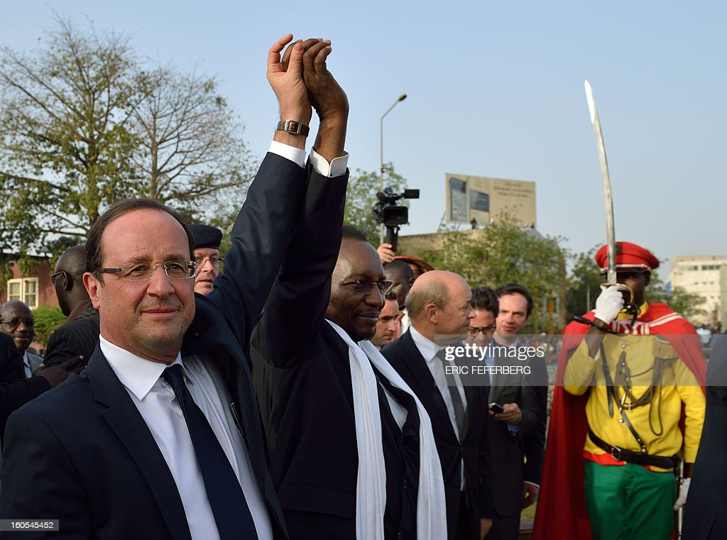 French President Francois Hollande (L) and his Malian counterpart Dioncounda Traore (C) raise their hands on February 2, 2013 after delivering a speech at the Independence Square in Bamako. French President Francois Hollande called on Africans to take over the fight against extremism as he received a rapturous welcome today in Mali, where a French-led offensive has driven back Islamist rebels from the north. AFP PHOTO / ERIC FEFERBERG