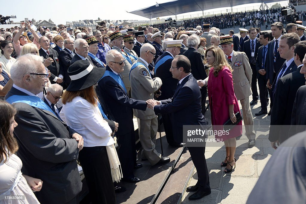 French President Francois Hollande and his partner Valerie Trierweiler meet with veterans during the Bastille Day parade at the Place de la Concorde, on July 14, 2013 in Paris.