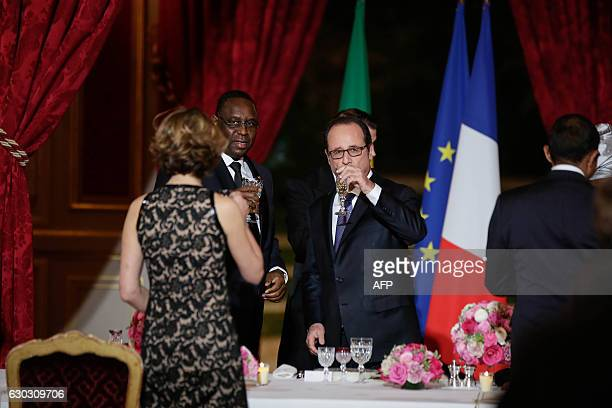 French President Francois Hollande and his Senegalese counterpart Macky Sall toast prior a state dinner at the Elysee Palace in Paris on December 20...