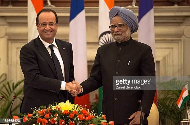 French President Francois Hollande and Indian Prime Minister Manmohan Singh shake hands after the signing of agreements at Hyderabad House on...