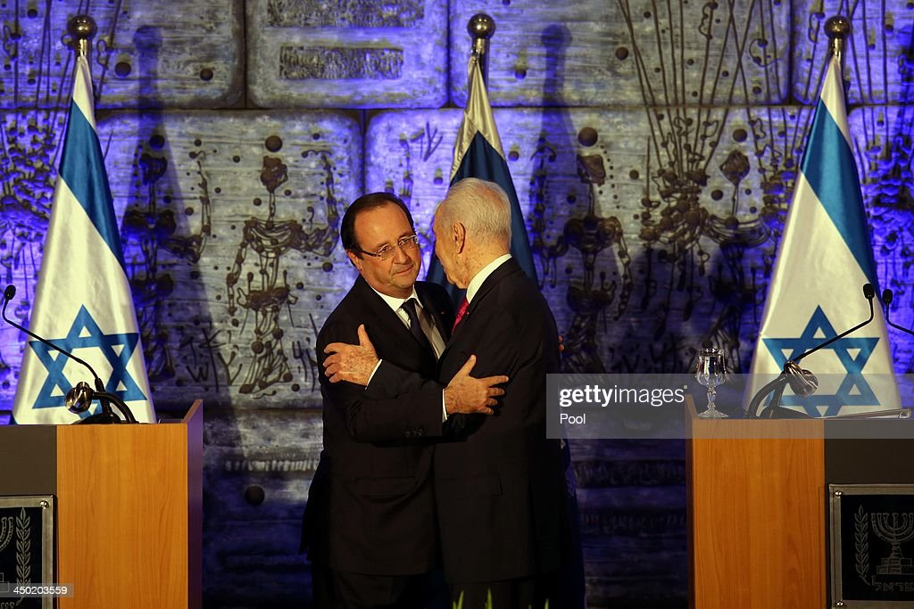 French president Francois Hollande (L) and Israeli President Shimon Peres (R) embrace after delivering joint statements to the media during a welcome ceremony for the French president at the Israeli president's residence on November 17, 2013 in Tel Aviv, Israel. Hollande landed at Israel's Ben Gurion airport for a three-day visit in Israel and the West Bank.