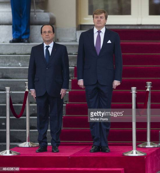 French President Francois Hollande and King WillemAlexander of The Netherlands listen to the national anthems during the welcome ceremony at the...