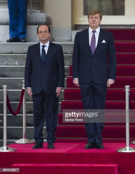French President Francois Hollande and King WillemAlexander of The Netherlands listen to the national anthems at the Noordeinde Palace at the start...