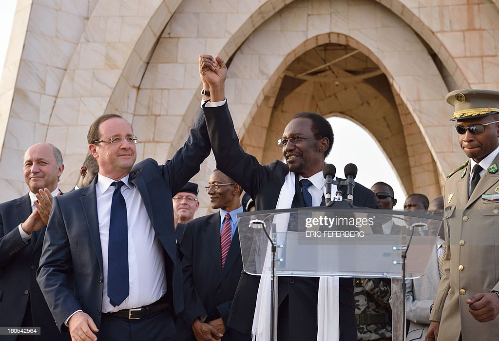 French President Francois Hollande (L) and Malian President Dioncounda Traore (C) wave to the crowd after their speech on February 2, 2013 in Bamako. Hollande called on Africans to take over the fight against extremism as he received a rapturous welcome today in Mali, where a French-led offensive has driven back Islamist rebels from the north. AFPPHOTO / ERIC