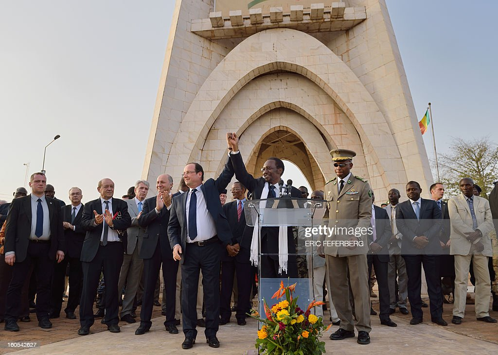 French President Francois Hollande (C, left) and Malian President Dioncounda Traore (C) wave to the crowd after their speech on February 2, 2013 in Bamako. Hollande called on Africans to take over the fight against extremism as he received a rapturous welcome today in Mali, where a French-led offensive has driven back Islamist rebels from the north.