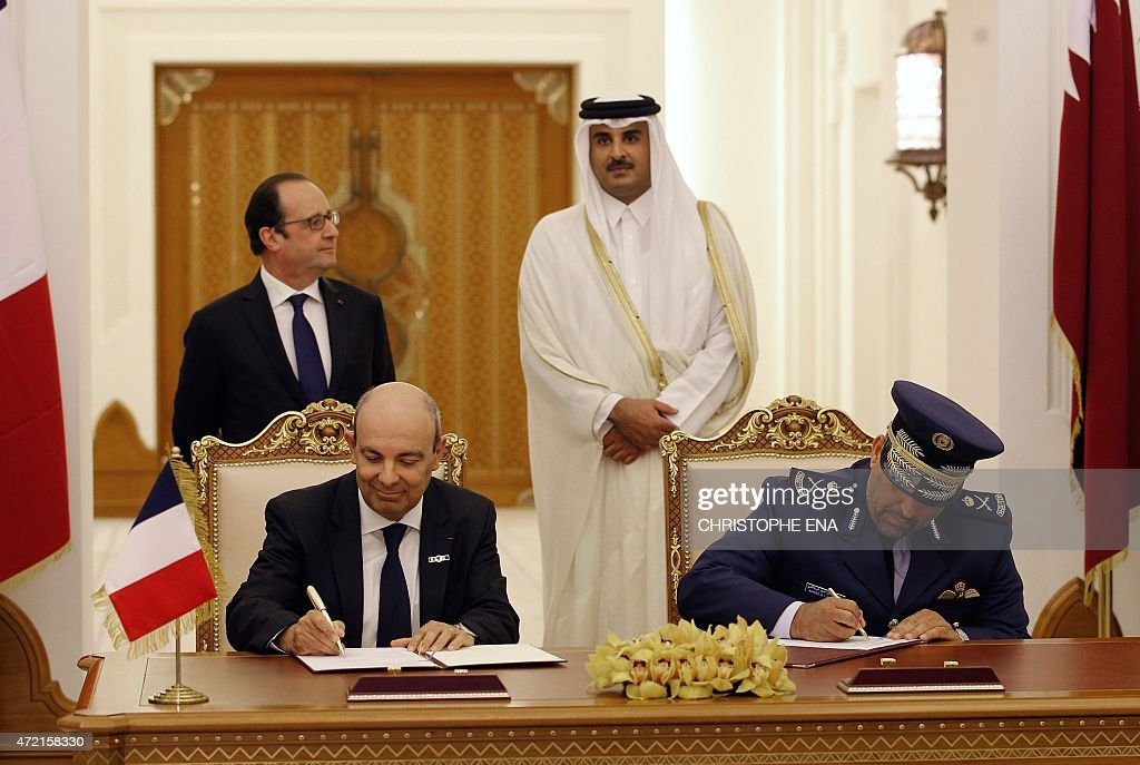 French President Francois Hollande (Rear L) and Qatar's Emir Sheikh Tamim bin Hamad al-Thani (Rear R) look on as CEO of Dassault Aviation, Eric Trappier (L) and Qatar's Gen. Ahmad Al-Malki sign an agreement at the Diwan Palace in Doha, on May 4, 2015. Hollande arrived in Qatar to oversee the signing of a multi-billion-euro deal to sell 24 Rafale fighter jets to the gas-rich emirate.