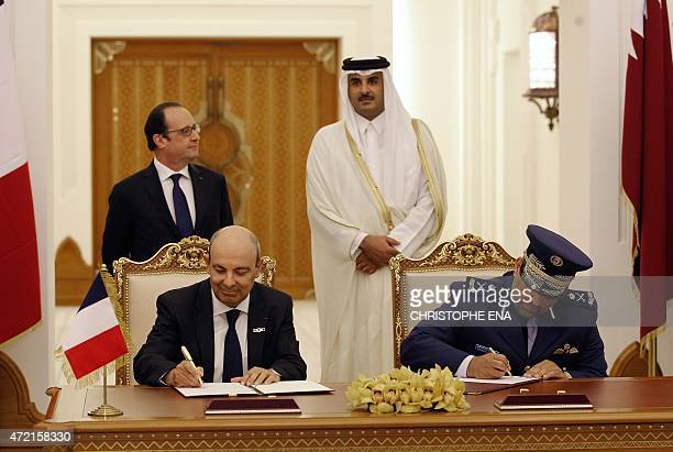 French President Francois Hollande and Qatar's Emir Sheikh Tamim bin Hamad alThani look on as CEO of Dassault Aviation Eric Trappier and Qatar's Gen...