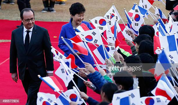 French President Francois Hollande and South Korean President Park GeunHye are greeted by South Korean children holding two countries flags during a...
